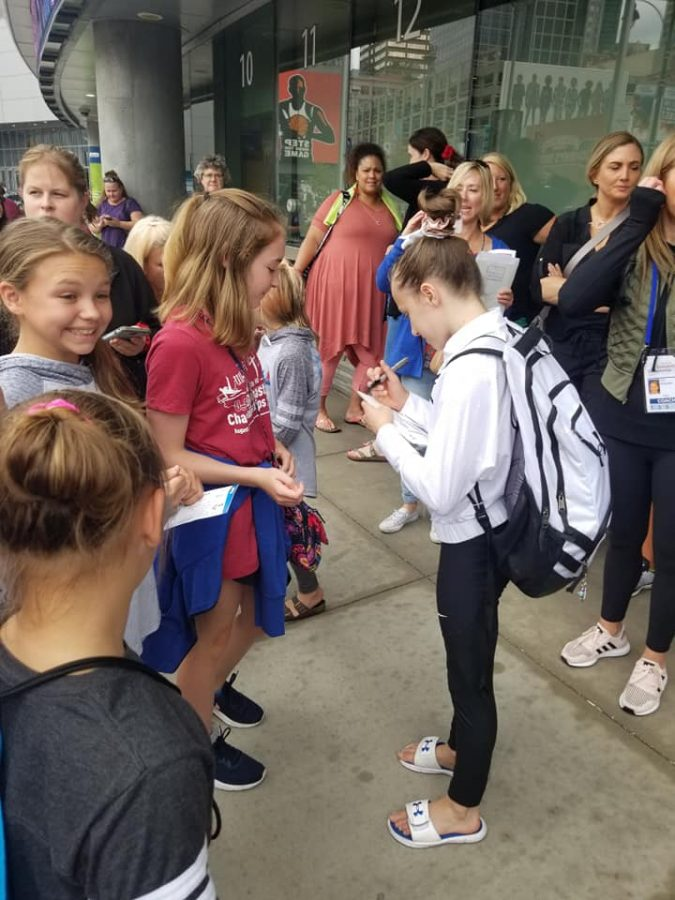 Ninth grade gymnast Ella Zirbes signs autographs for her fans at the U.S. Championships. This was held in Kansas City Missouri last August. Fans crowd Zirbes with shirts and merchandise to sign.