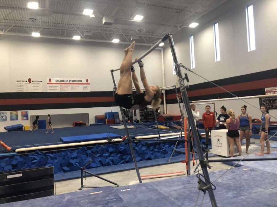 Junior+Heather+Wiehe+practices+for+the+season+by+working+on+her+up+rises+on+the+uneven+bars+in+the+gymnastics+gym.+Coach+Dusty+Dennis+prepares+with+gymnasts+for+the+upcoming+season.
