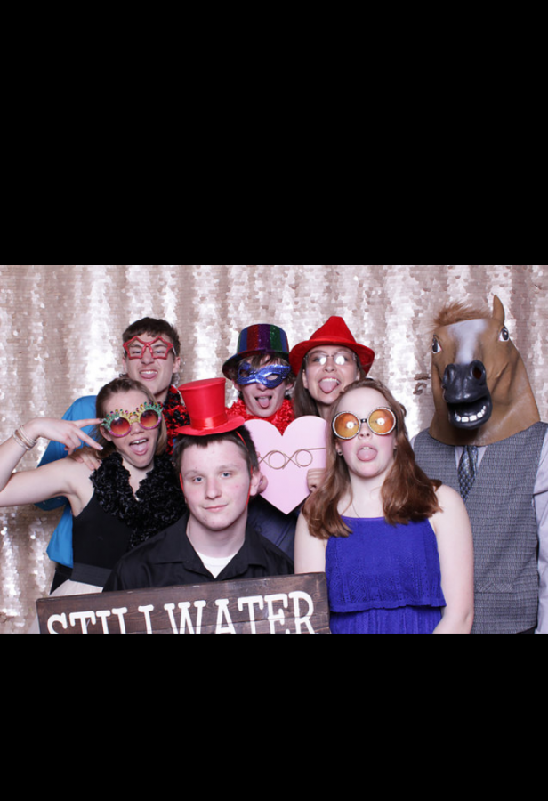 Senior Issac Sauer , senior Tucker Farver, senior Celia Gear and friends take pictures in the photo booth during last year's Snoball dance. The Snoball dance is one of the year's most popular events, with tickets commonly selling out.