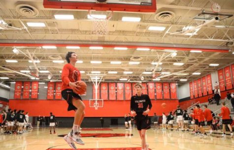 Managers help the team get better during the season. Junior Nick Cherry learns how to get better on lay-up before the game at the high school with freshman Max Shikenjanski on the right.