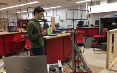 Robotics captain junior Ben Abbott is testing the robots programming to make adjustments. The robot can sense the light that reflects back at the sensors from the reflective tape.