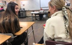 Engaging in conversation during Journalism class, seniors Alayna Christian and Sophie Watkins discuss the different stereotypes associated with high school girls on Feb. 11.