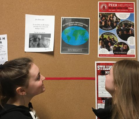 Juniors Ayuna Lamb-Hickson and Olivia Lind view the diversity poster for BLAST week. The BLAST week presentations are featured during the Black History Month presentation.