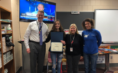 Junior Ava Shelton stands with principal Rob Bach, marketing teacher Debbie Drummerhausen and Stephanie Musgrove as she accepts her award from the essay contest.