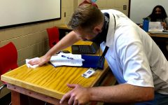 Math teacher Peter Hamilton takes precautions by wiping down desks. Hamilton ensures safety for students in the classroom.