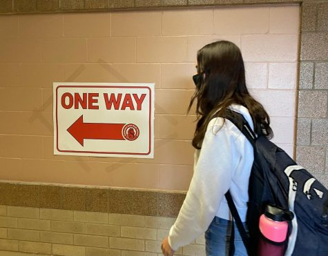 Junior Greta Sorenson abiding by the new preventions in the school. She is wearing a mask and following the one-way hallways, keeping herself and others safe from COVID-19.