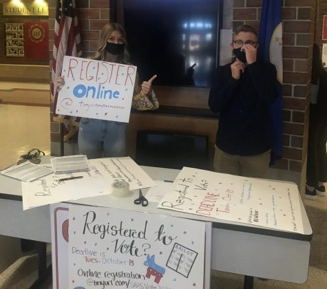 Seniors Alex Steil and Natalie Loehr try to bring in students to their voting booth. On Oct. 12 and 13, the Young Democrats and Young Republicans ran a booth in the main rotunda to register seniors that are eligible to vote.