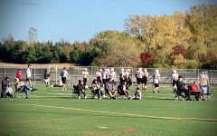 Captured in this photo is the varsity football team practicing for their game against White Bear on Oct. 9. They are practicing on one of the many practice fields, located in the back of the school. As seen in the photo, the coaches have masks or face coverings on, along with some of the parents and family members watching the practice.
