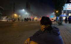 Senior Missa Lunzer watches the protests from a distance. She sits on the side of the street to recover from being tear gassed. The streets are full of smoke yet people stay out to chant.