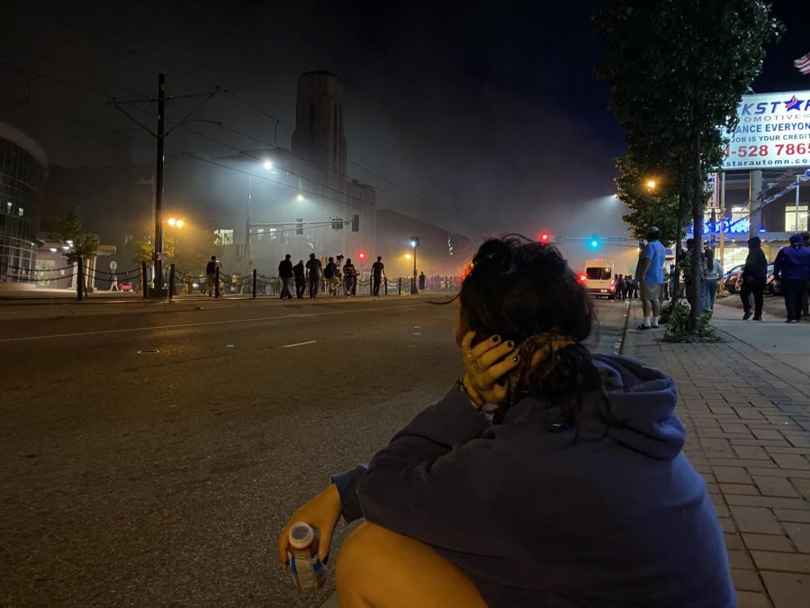Senior+Missa+Lunzer+watches+the+protests+from+a+distance.+She+sits+on+the+side+of+the+street+to+recover+from+being+tear+gassed.+The+streets+are+full+of+smoke+yet+people+stay+out+to+chant.+