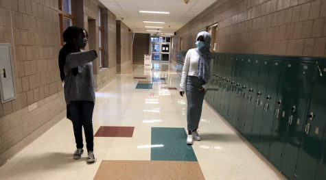 Link Leader Sadyia Farah showing freshman Safiyo Farah where to go for her class. They are keeping their distances apart from each other and wearing masks.