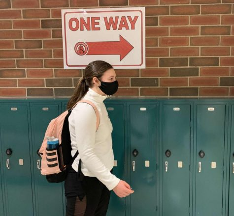 "Students walk down ""one way"" directed hallways in SAHS to follow the safety precautions for Covid-19, examples of the precautions set in place are; wearing a mask and many more."