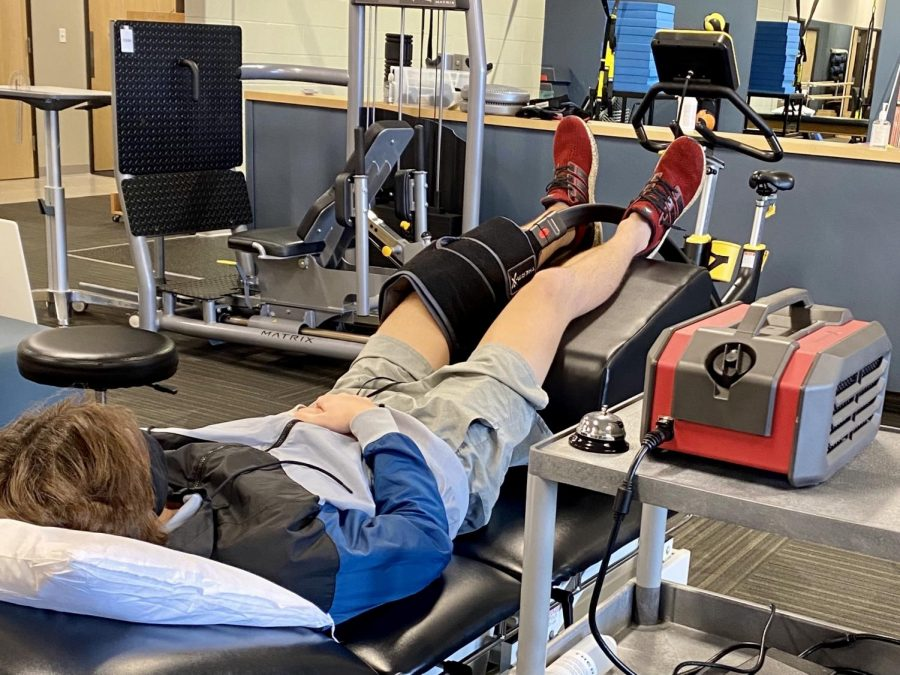 Photo credit to Beth Dierkhising. Drake takes part in physical therapy twice a week which will help him regain strength and mobility. Pictured he is using an ice machine to reduce swelling after therapy.