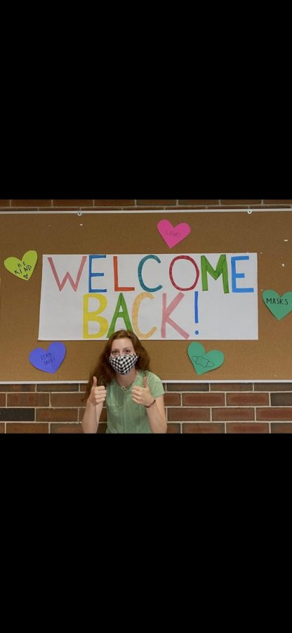 Student Council Co-President Brynn Wurgler posing in front of a welcoming sign after decorating the school for the return of students.  This sign is one of many made by Student Council greeting hybrid students everyday. ¨We just wanted to welcome back everybody.  So weve just been trying our best to make do with like the different restrictions that we have to deal with.¨ - Brynn Wurgler
