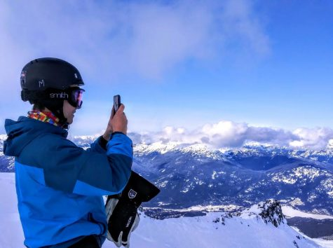 Junior Jacob Carlson stops skiing and takes a picture of the scenery while being photographed by his father.