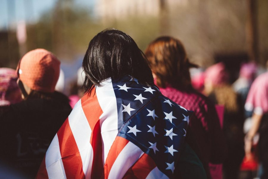 A woman wearing an American flag. American democracy is a point of pride for many Americans.
