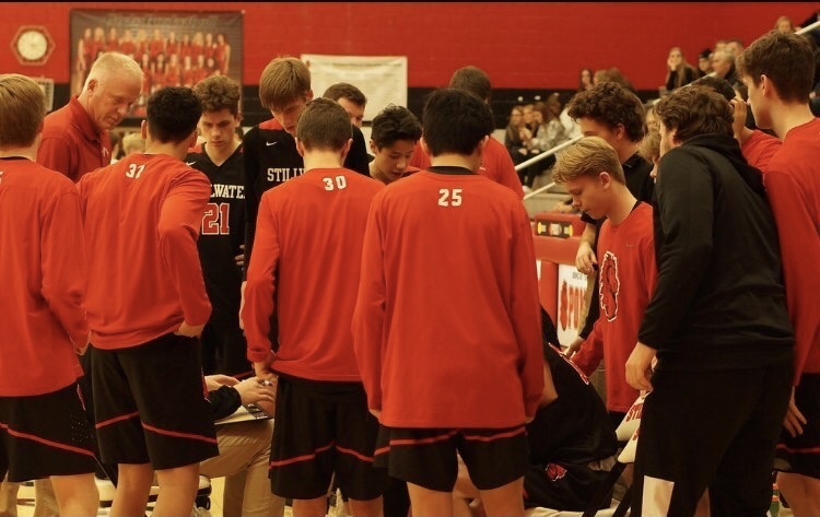 The varsity basketball team huddles in preparation for a game. This year, the team's start has been delayed due to Covid.