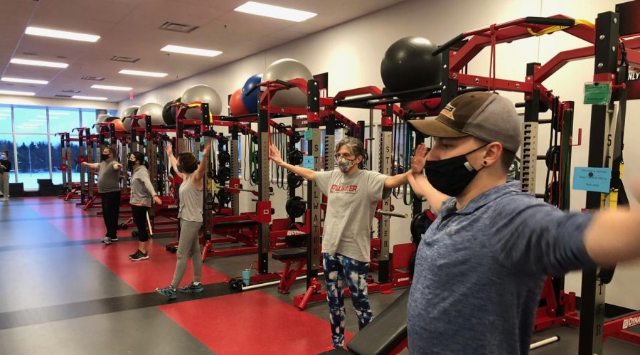 Zack Quaderer, Adult Boot Camp Coach, goes through his warm-up in preparation for their sessions workout on Feb. 17. Quaderer leads this workout every Wednesday and Friday evening at the PAC.