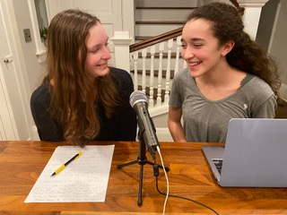 The Herbert sisters sit in their kitchen recording their newest episode. Hannah (left) has the script outline in front of her, and Paige (right) has the computer monitoring the audio and time they've been recording.