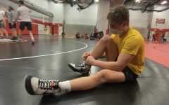 Sophomore Zach Hunter gets ready for wrestling practice while wearing a mask due to Governor Walz mask mandate.