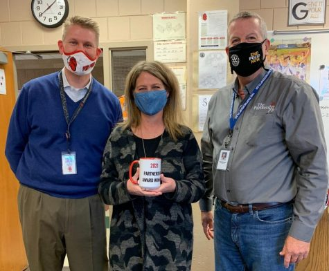 Math teacher Kathy Meyer stands beside principal Rob Bach and executive director Rick Robbins after being suprised with the news that she had been nominated and won a Partnership Award. Along with the recognition and honor bestowed upon her, she also receives an excellent mug.