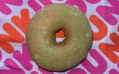 This image shows an overhead picture of the new Dunkin Matcha Topped Donut.  The vibrant green and exotic flavor makes people curious and eager to give this donut a try.