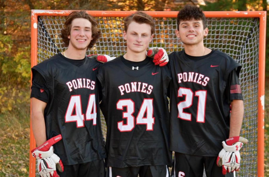 Senior Captains Alex Corbett, Gunner Arnes and Isaac Albers stand together in front of the net getting ready to lead the lacrosse team in a strong season. They hope to have a strong season and team this year.