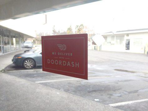 DoorDash advertisement sticker on restaurant window.