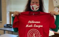 Stephanie Nord, the advisor for the stillwater math league, holds up a team T-shirt in the classroom where they normally meet. Due to COVID-19 the team did not print out new shirts for the 2020-21 season.