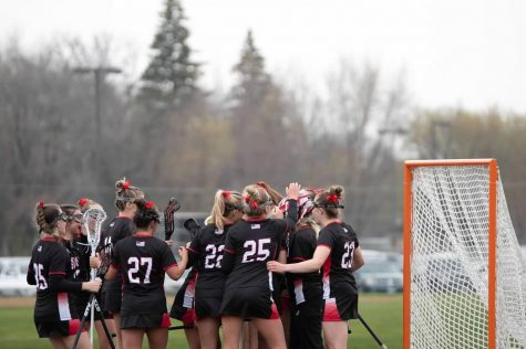 The girls lacrosse team wins against Irondale in their first game of the season. They celebrate the win with their goalie Hannah Beard.