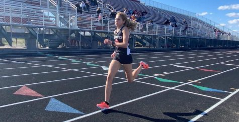 Senior Ana Weaver crosses the finish line of the 1 mile. Weaver completed a time of 5 minutes flat at her home track.