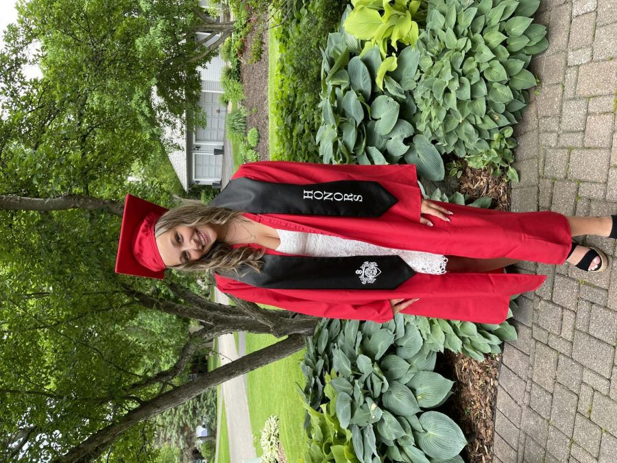 Senior Emma Kindler in her last day of school in your cap and gown.