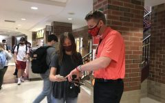 Principal Rob Bach helps junior Ella Hamilton in the hall. demonstrating how Bach is attentive to his students' needs.