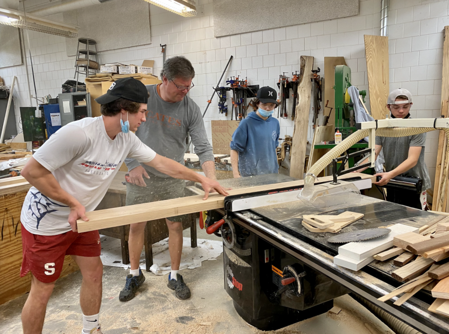 Senior Alex Corbett works with carpenter Marty Peterson, from Cates Fine Homes, and freshmen Carson Bahr and Grant Heinert on the river epoxy conference table in the school's woodshop room.