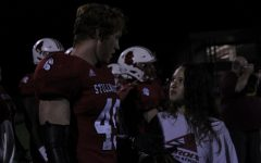Senior Grace Volkman connects with junior player Charlie Gleason on the sidelines during the game. Grace was recently given the title of the 2021 football manager and she spends practices and game days working hard.