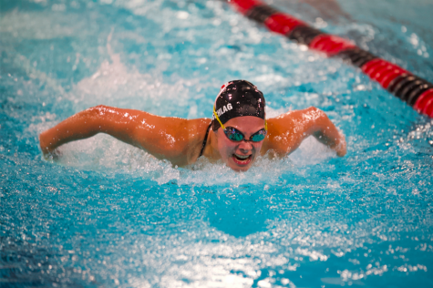 Junior grader Lucy Siedschlag swims the 100 yard butterfly at a dual meet against Park. Siedschlag takes a deep breath as she fights for first place with a time of 1:05.97.