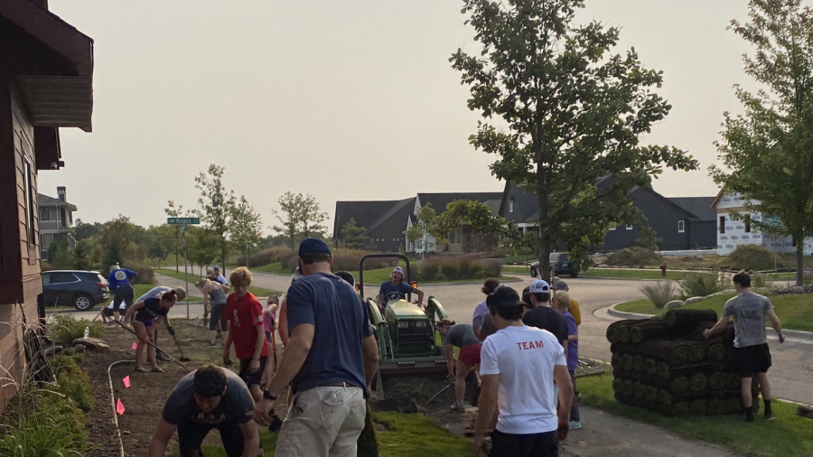 The hockey team and members of the community lie down sod for wounded veteran Mike Polehna.